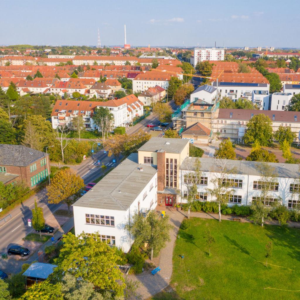 Beide Schulgebäude waren Bestandteil einer monumentalen Planung mit einer Platzanlage und einer großen Kirche als Zentrum der Gartenstadt Gesundbrunnen.